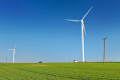 Windmill turbine on blue sky. Wind energy. Modern green power. Stock Photos