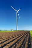 Windmill turbine on blue sky. Wind energy. Modern green power. Windmill turbine on blue sky. Wind energy. Modern green power in rural environment Royalty Free Stock Photo