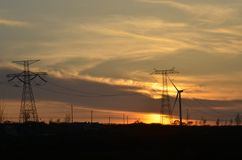 Windmill Turbine and Electric power lines Stock Image