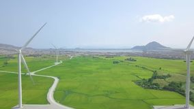 Windmill turbine on energy plant power in agricultural field. Aerial view wind power generating farm on green field, sea. And mountain landscape. Generation stock video footage