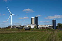 Windmill Turbine Wind Green Energy by Farm. A modern wind turbine windmill producing green energy power and reducing dependency on oil and gas and other fossil royalty free stock photo