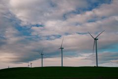 The windmill turbines are close-up against the backdrop of sunset clouds. royalty free stock photos