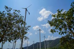 Windmill turbines white steel post technology to generate clean renewable ecological energy with green mountain, blue sky Stock Photos