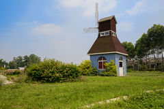 Windmill in verdant lawn on sunny summer day Stock Photos
