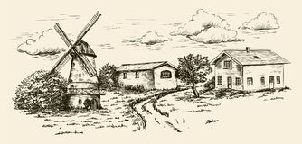 Windmill, village houses and farmland Stock Image