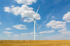 Windmill on the wheat field with hay bales Royalty Free Stock Images