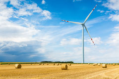 Windmill on the wheat field with hay bales Royalty Free Stock Photos