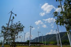 Windmill white post and solar cell panel technology to generate clean renewable ecological energy on grass yard. With green mountain, blue sky and white cloud Stock Photo