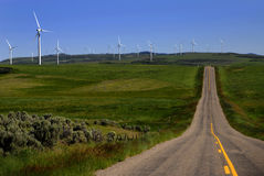 Windmill for Wind Power on top of lush green hill road Stock Photo