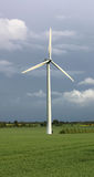 Windmill, wind turbine. Modern windmill or wind turbine in the countryside. dark blue sky and green field royalty free stock photos