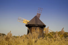 Windmill wooden traditional industrial. Architecture behind cane in open air museum Stock Photo