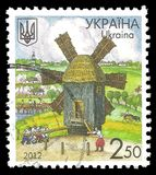 Windmill and working peasants. Ukraine - stamp 2012: Color edition on Wooden constructions, shows Windmill and working peasants Stock Images