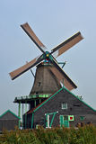 Windmill in Zaanse Schans, Holland. Old wooden windmill and house in Zaanse Schans, Holland against blue skies Royalty Free Stock Photo