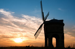 Windmilll. An old disused windmill silhouetted against a brilliant sunset and blue sky Stock Photos