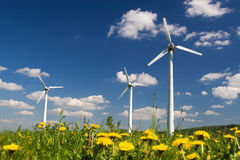 Windmills. Wind Farm against blue sky with white clouds and yellow flowers on the ground stock image