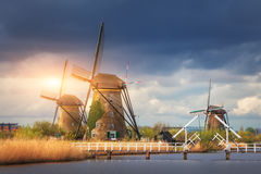 Windmills against cloudy sky at sunset in Kinderdijk, Netherland Royalty Free Stock Images
