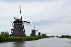 Windmills along the canals of the World Heritage Kinderdijk, Netherlands. Travelling to Holland visiting the windmill park of the UNESCO World Heritage stock image