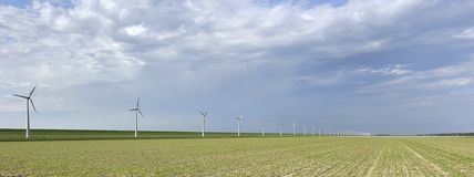 Windmills along a dike Royalty Free Stock Photos