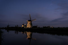 Windmills along the water in Kinderdijk at twilight Stock Image