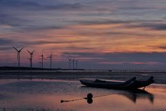 Windmills Behind Canoe Boat during Sunset Stock Photos