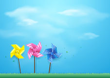 Windmills blowing in the wind on blue sky. Paper art style Stock Image