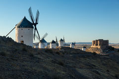 Windmills and castle at Consuegra, La Mancha, Spain. Preserved historic windmills with castle on hilltop above Consuegra in Castilla-La Mancha, Spain Royalty Free Stock Photos