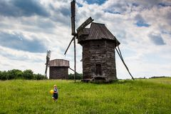 Windmills and children in the field under the. Windmills in the national museum of culture and life Pirogovo, Kiev, Ukraine, Europe Stock Photography