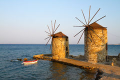 Windmills of Chios. Old Windmills of Chios Island,Greece and a boat at coast of Chios Town royalty free stock photos