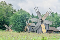 Windmills close up, green forest, wild vegetation, blue clouds Royalty Free Stock Photo