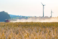 Windmills and combine on the field Stock Photography
