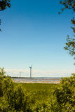 Windmills In The Distance. The windmills were quite still during a very cold summer day in Oulu, Finland royalty free stock photography