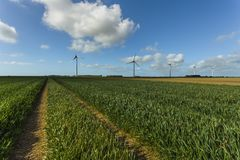 Windmills for electric power production in agricultural fields in Normandy, France. Renewable energy sources, industrial. Agriculture concept. Environmentally Royalty Free Stock Photography