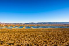 Windmills farm and water reservoirs along a highway in Mojave desert Stock Photography