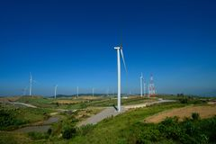 Windmills farm or Wind turbine power generators standing on green mountain against a blue sky, Located Khao Kho, Thailand. Windmills farm or Wind turbine power Royalty Free Stock Photo