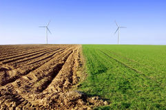 Windmills on the field conceptual image. Windmills on the plowed and green field Royalty Free Stock Photos