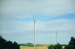 Windmills in a field for electric power production Royalty Free Stock Photo