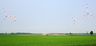 Windmills in the field and a tractor in the middle Stock Image