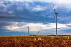 Windmills in the fields with dramatic rain clouds in the backgro. Und Stock Photos