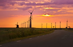 Windmills in front of bright sunset Royalty Free Stock Photos