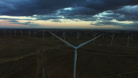 Windmills generating clean renewable energy at dawn. Aerial view of windmills generating clean renewable energy during sunrise shot on drone camera stock video