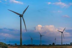 Windmills on green at sundown royalty free stock image