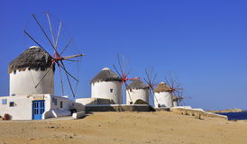 Windmills on a hillside near the sea. Mykonos. Stock Photo