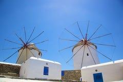 Windmills on Island of Mykonos. Two whitewashed windmills on the Greek island of Mykonos with cloudless blue sky background Stock Image