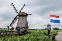 Windmills in marsh landscape with Dutch flags Royalty Free Stock Images
