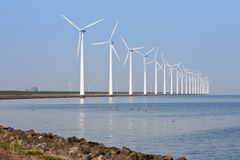 Windmills mirroring in the calm sea royalty free stock image