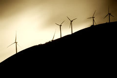 Windmills on mountainside. A wind turbine park with windmills behind a hill and mountainside Royalty Free Stock Images