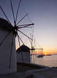Windmills at Mykonos at sunset at sea and the ship Royalty Free Stock Photography