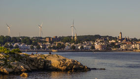 Windmills near the ocean and city Stock Images