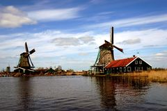 Windmills near river. Buildings and windmills in Zaanse Schans ethnographic museum in Netherlands stock images