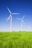Windmills over green fields Royalty Free Stock Image